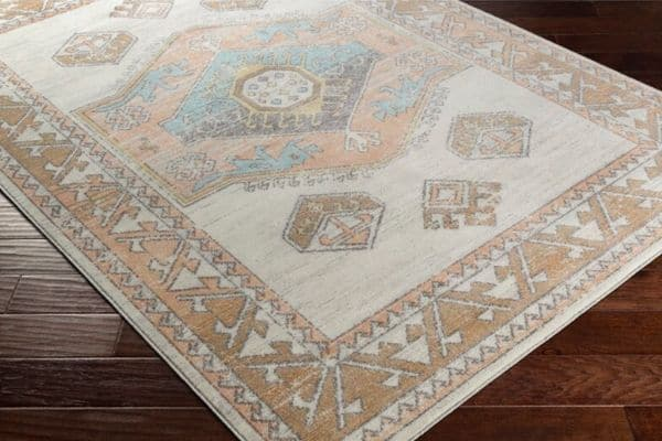 A southwestern style rug with muted colors of gold, pink, blue and ivory.