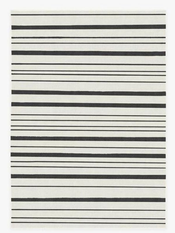 A white rug with black stripes of different widths.