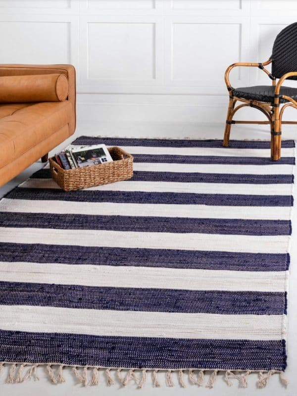 A coastal Rug with thick blue and white stripes and tassels on the ends.