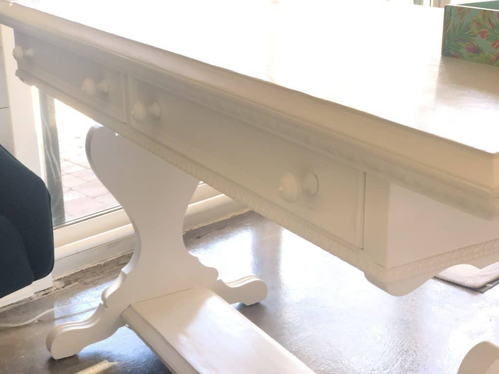 A closeup of the drawers and trim in the front of the vintage desk.