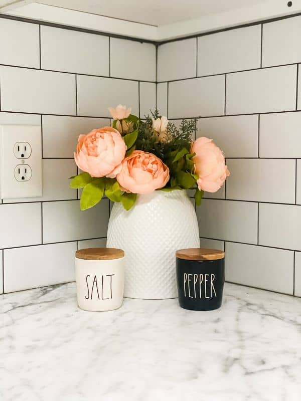 Rae Dunn salt and pepper next to a vase with peonies.