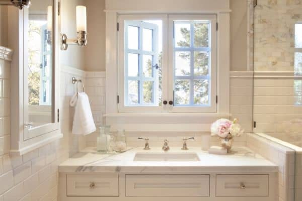 A bathroom sink with a window above and revere pewter painted on the walls.