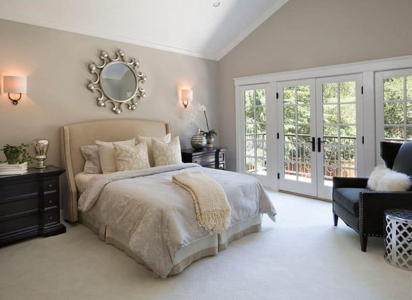 A bedroom with french doors and revere pewter painted on the walls.