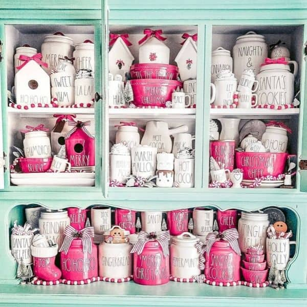 Pink and white Rae Dunn pottery displayed in a mint green colored hutch.