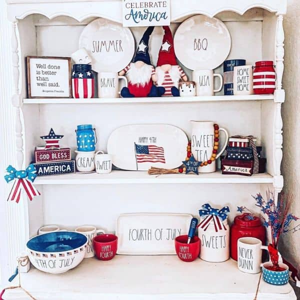 Patriotic Rae Dunn pottery displayed in a white china hutch.