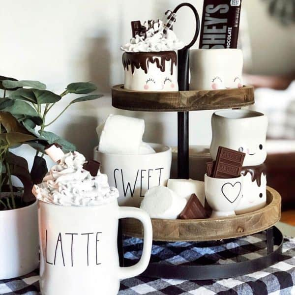 Rae Dunn mugs with chocolate and marshmellows on a tiered tray and buffalo check tableccloth.