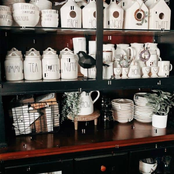 Rae Dunn plates, bowls, canisters and bird houses displayed on a black hutch with a wood counter top.