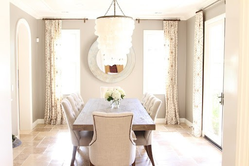 A dining room with a large shell chandelier and walls painted in Benjamin Moore Revere Pewter.
