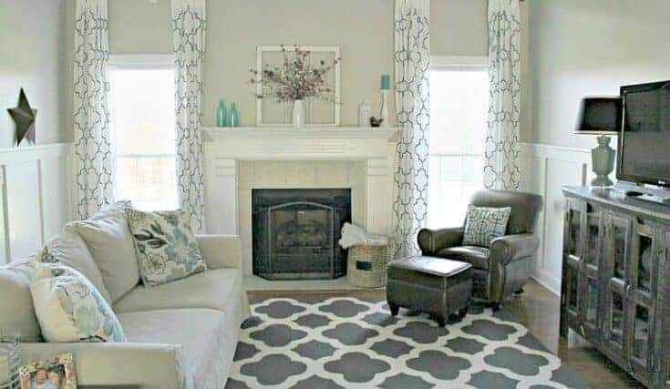 A family Room with a gray and white geometric rug and curtains with Revere Pewter on the walls.