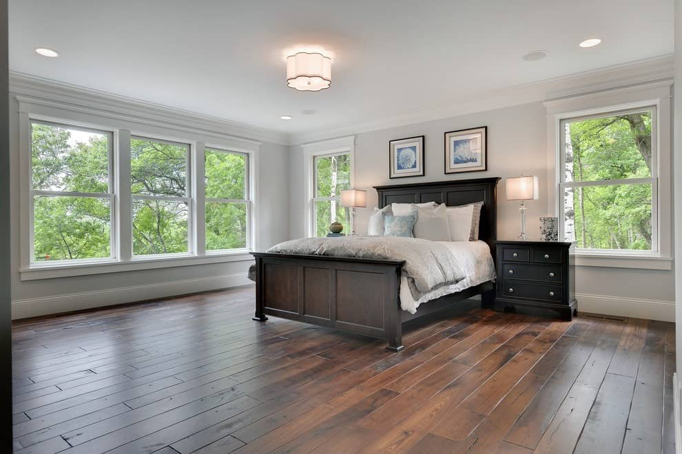 A bedroom with dark hardwood floors, lots of windows and revere pewter paint color.