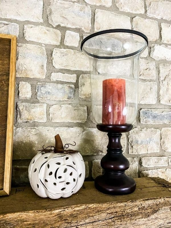 The ceramic white pumpkin and an orange candle in a large urn, fall mantel decorating tips.