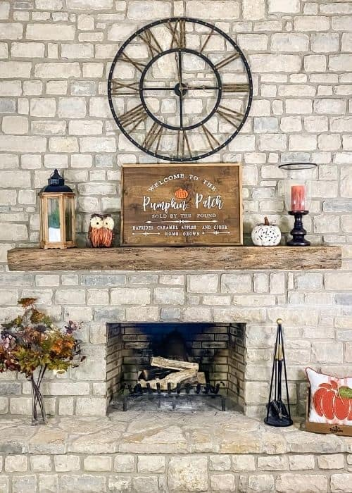 A front view of my fireplace with a sing, owl, pumpkin candle and lantern on the mantel.