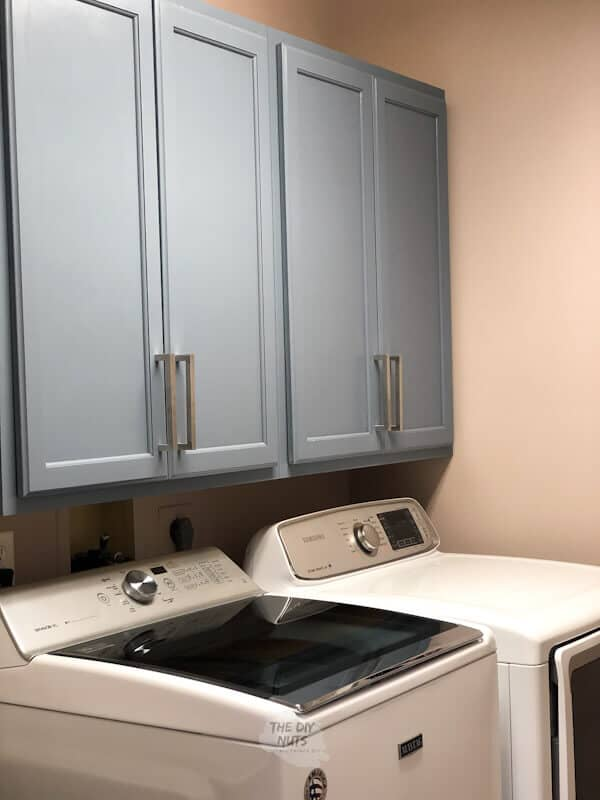 A laundry room with cabinets above the washer and dryer with silver cabinet pulls.
