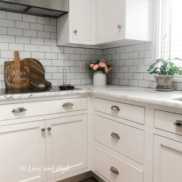 A white kitchen with silver knobs and pulls, white carrera countertops and white subway tile backsplash.