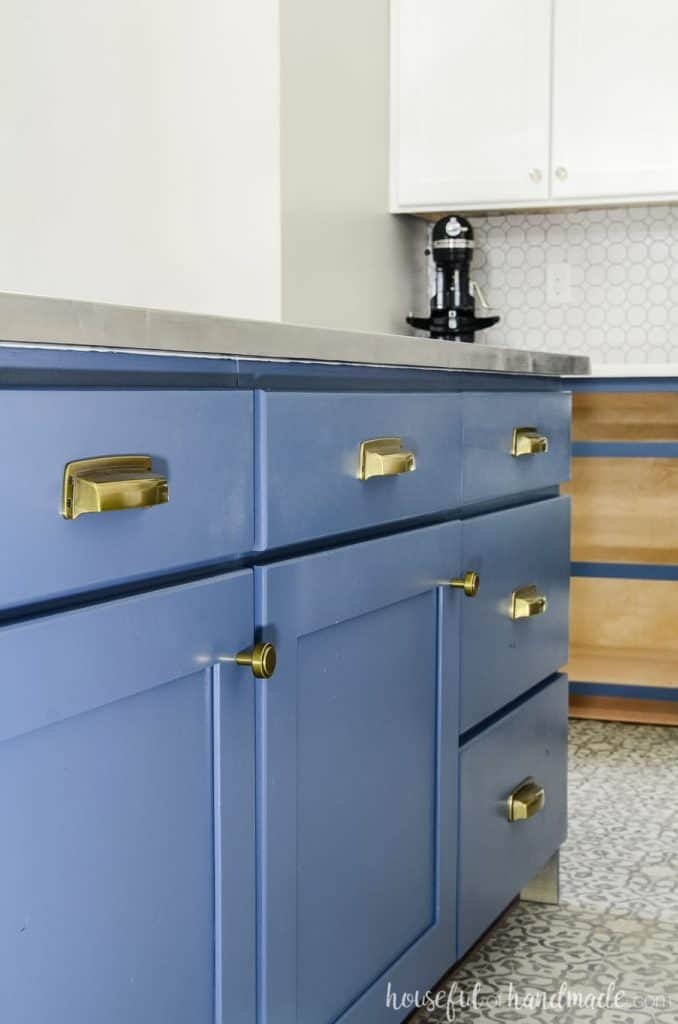 A blue island with gold cabinet hardware.