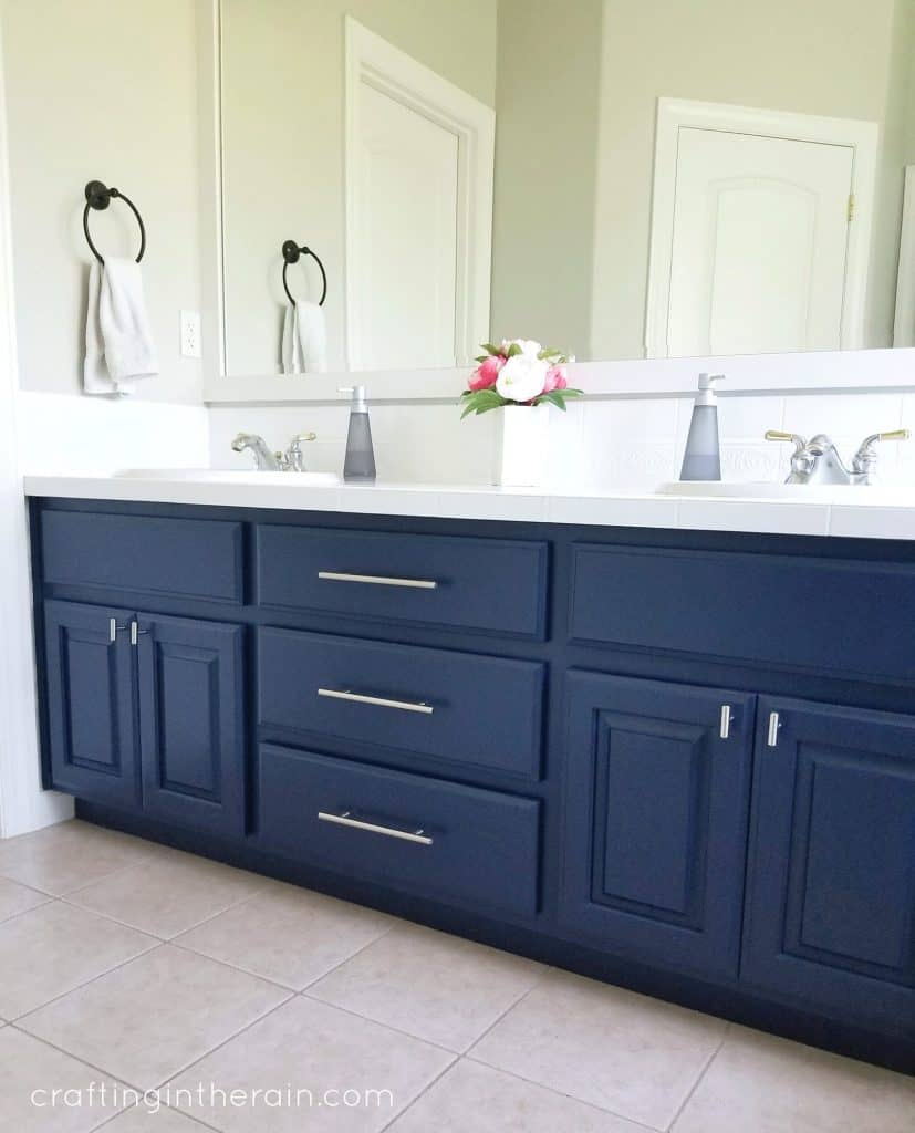 A navy blue vanity in a bathroom with silver handles and pulls that match.