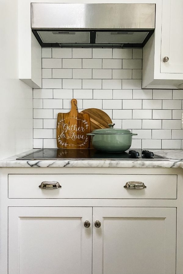 An aqua colored dutch oven on a stove top with white cabinets, white subway tile back splash and two cutting boards in the background.