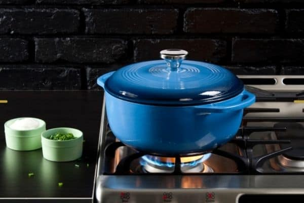 A bright blue Lodge dutch oven on a stove with black counters and a black brick painted back splash.