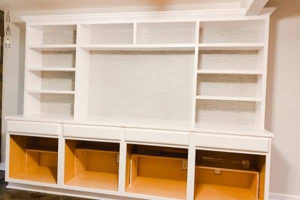The DIY built-ins without cabinet doors but with the wall paper installed.