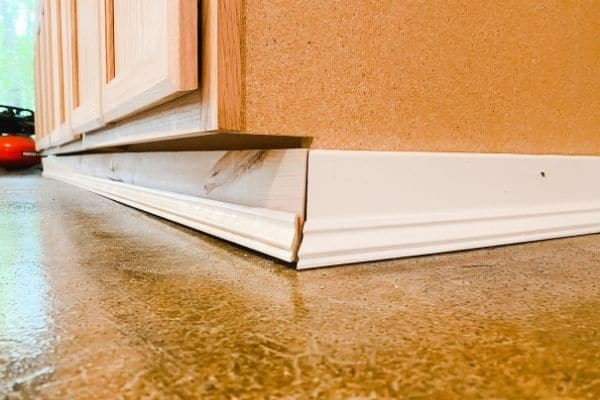 This shows re-installing the baseboards around the cabinets.