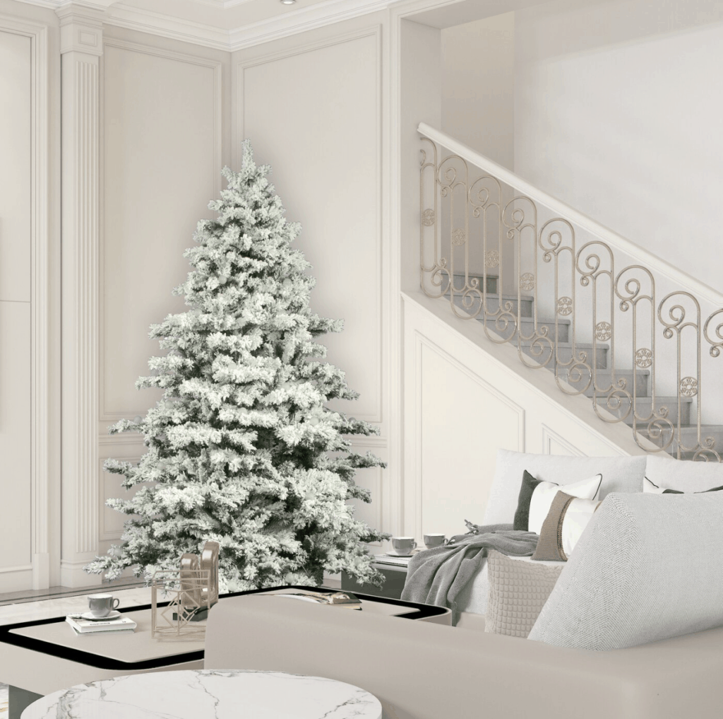 A Flocked Christmas tree with no lights against a white wall with picture frame molding.