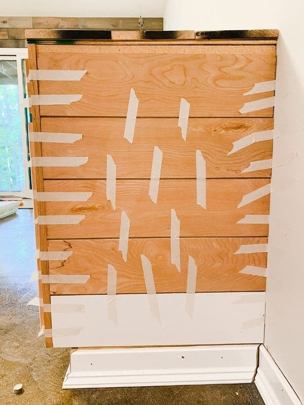 Here is the end of the cabinets with the shiplap being held on by tape to let the wood glue dry.