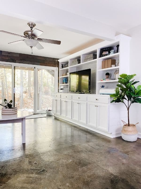 A view of my stained concrete floors with my white DIY built-ins and a fiddle leaf fig tree in a basket.