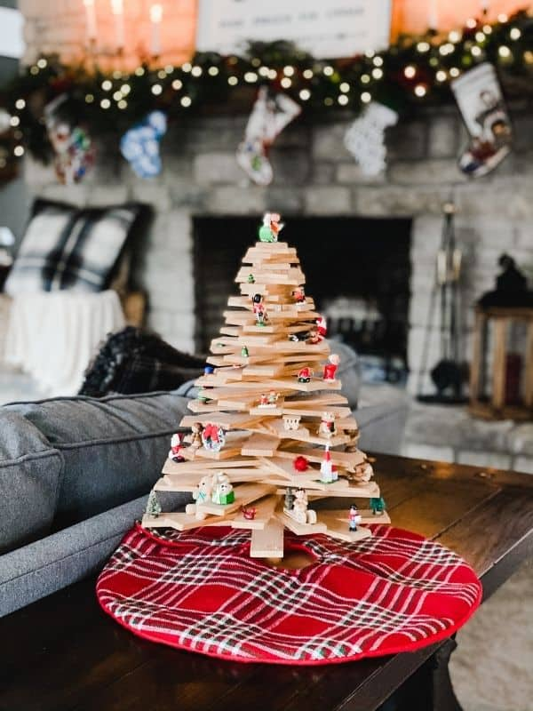 A wooden Christmas tree with a red plaid tree skirt.