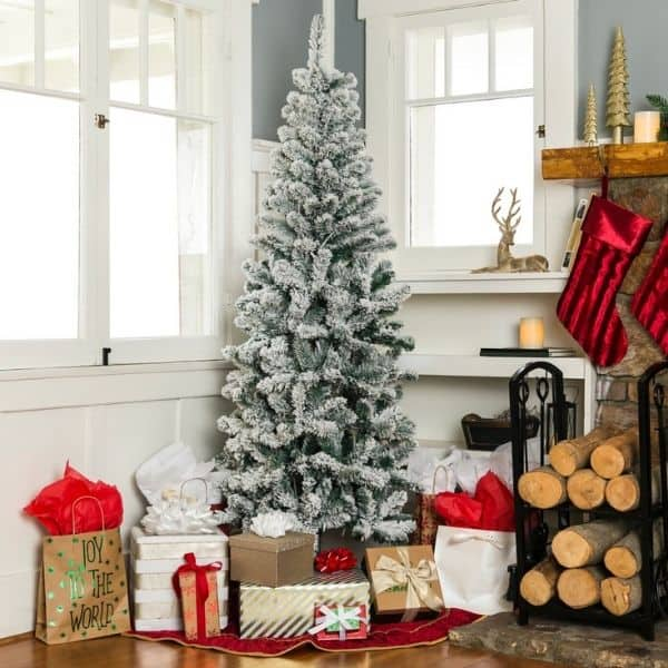 An unlit Flocked Christmas Tree with no ornaments surrounded by gifts.
