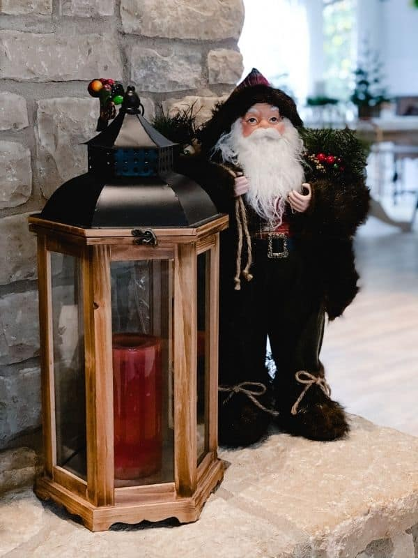 A Santa next to a lantern sitting on the hearth of my Traditional Christmas Mantel.