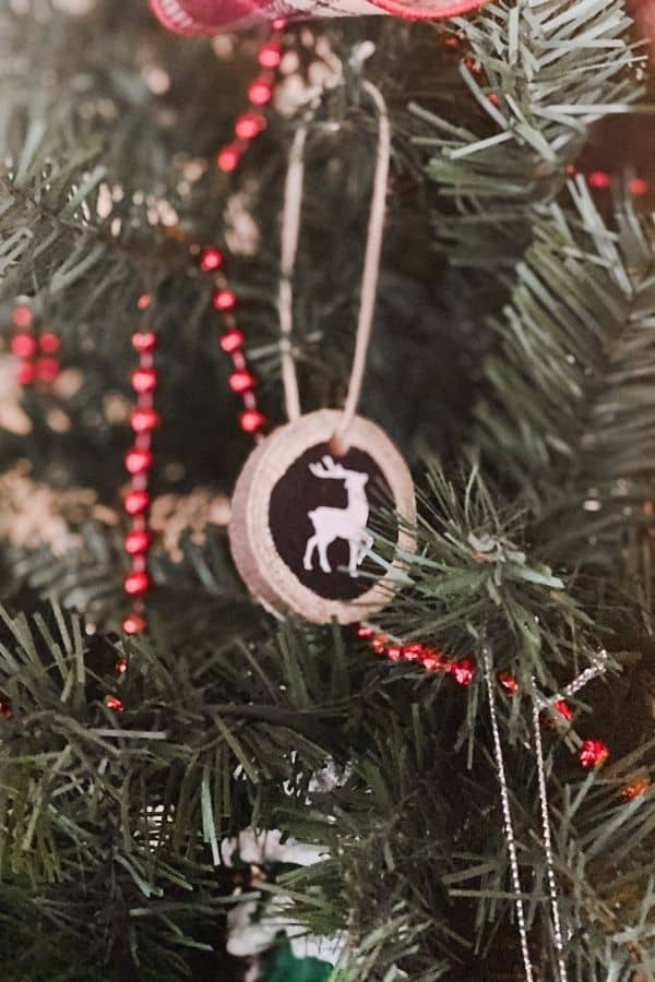 Tree slice ornament with a silhouette of a reindeer on it hanging on a Christmas tree.