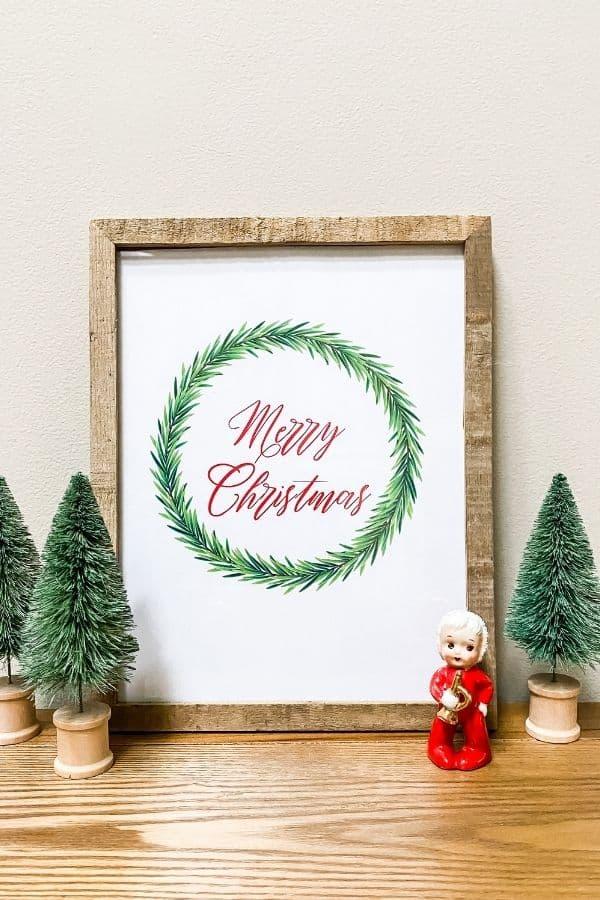 A farmhouse Christmas printable that says merry Christmas with a wreath around it.
