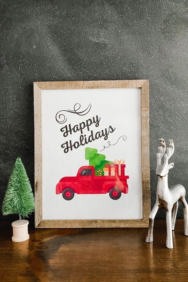 A farmhouse Christmas printable that says Happy Holidays with a red old truck and a christmas tree and packages in the bed of the truck.