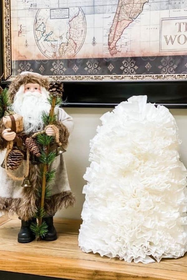 A Santa next to the coffee filter Christmas tree.