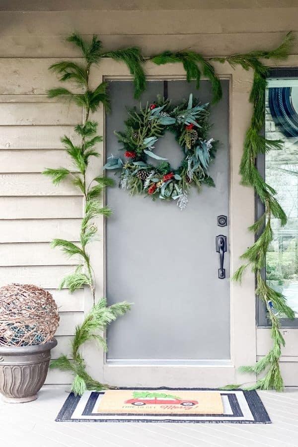The front door with a wreath and pine garland around the door.