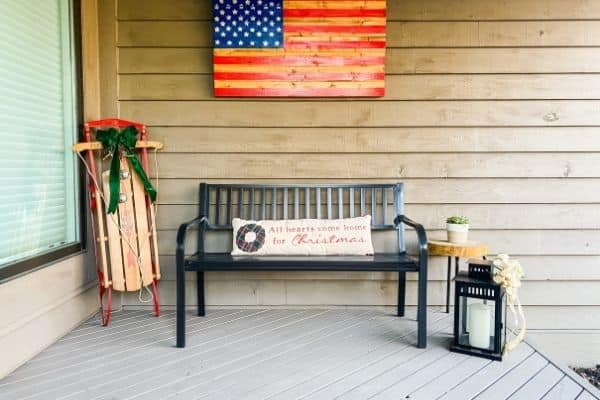 The front porch bench with a long lumbar pillow and a sled with a bow.