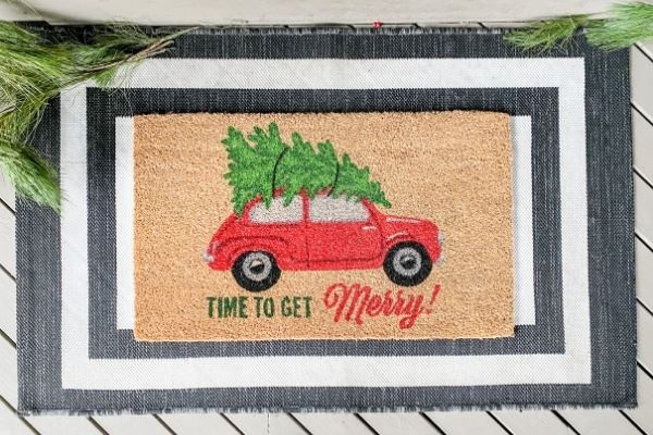 "The front door mats with a red car and Christmas tree with the saying ""time to get Merry!""."
