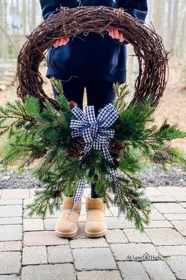 My daughter holding the winter wreath with a buffalo check bow.