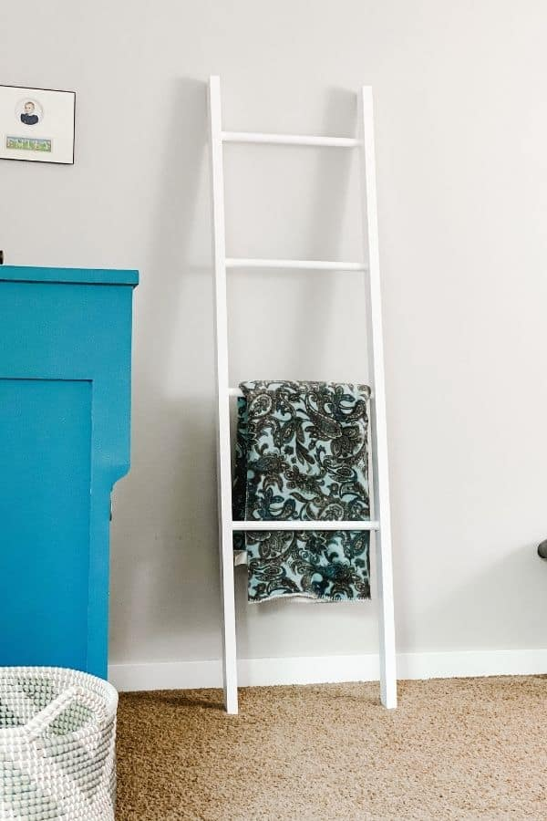A white painted blanket ladder next to a blue painted dresser.