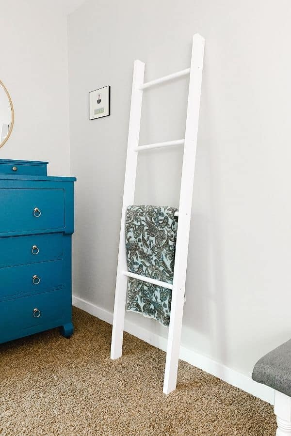 A white blanket ladder leaning on a light gray wall next to a blue painted antique dreser.