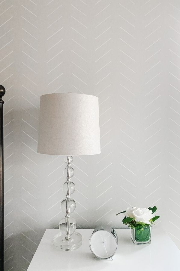 Guest bedroom headboard wall with a herringbone accent stenciled on in white.