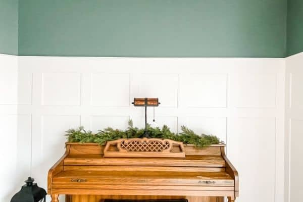 DIY Board and batten with blue green paint above and my piano with greenery on top.
