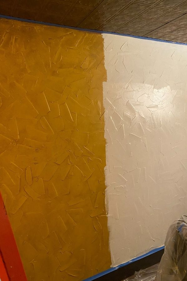This shows the yellow/gold walls half painted with the new Natural Linen color.