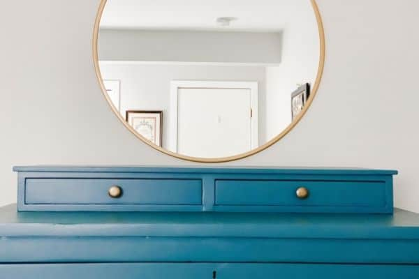 Guest bedroom dresser painted a blue gray color with a round gold mirror on the wall above.