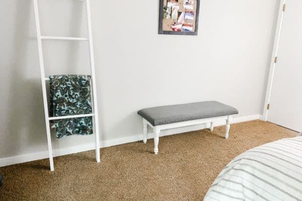 Guest bedroom wall opposite the bed with a bench and blanket ladder.