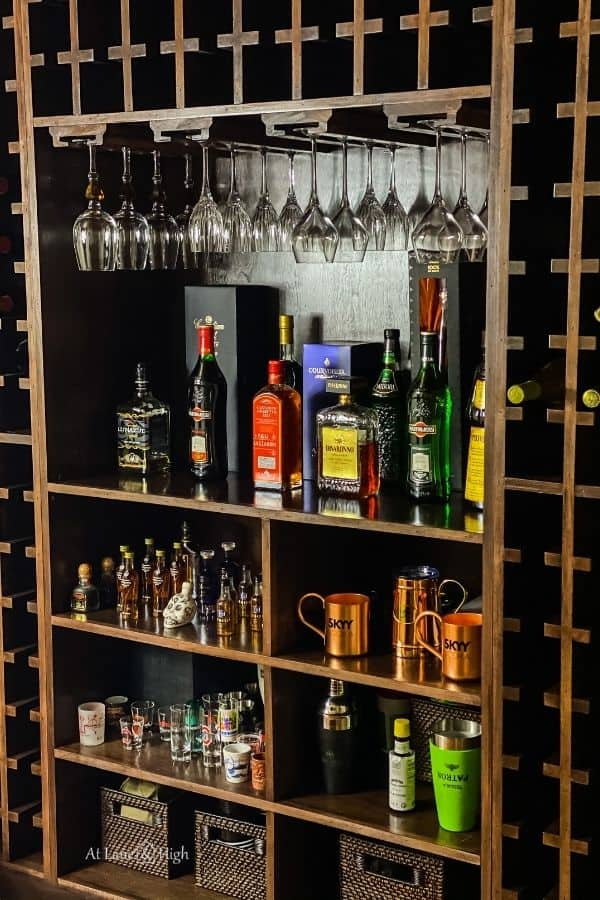 The center of the shelving unit that holds hanging stemware, liquor and some serving items in baskets.