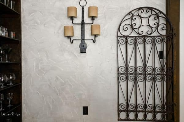 The aged wall with the iron gate p against it and the wrought iron light fixture.
