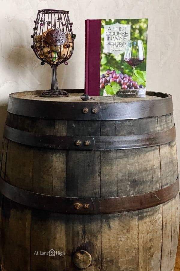 This shows a wine book and a decorative holder for wine corks in the shape of a wine glass on the barrell.