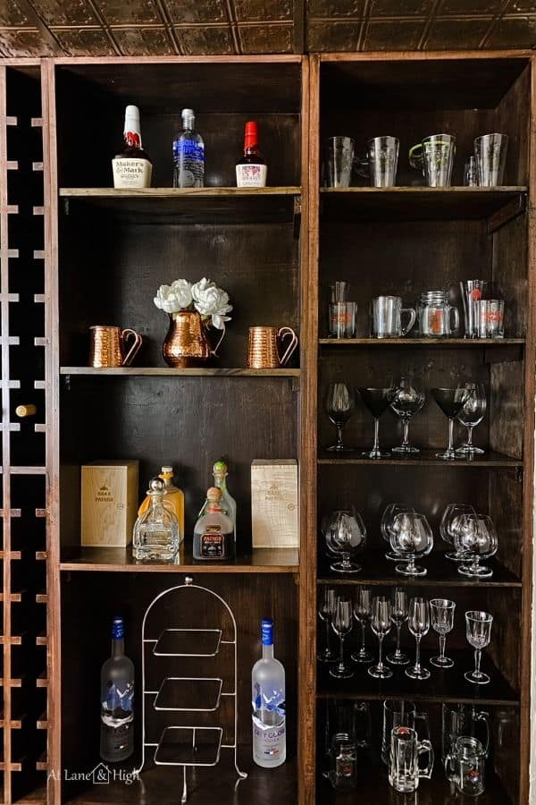 This shows the wine cellar shelves on the far right holding all the stem ware and some liquor bottles.