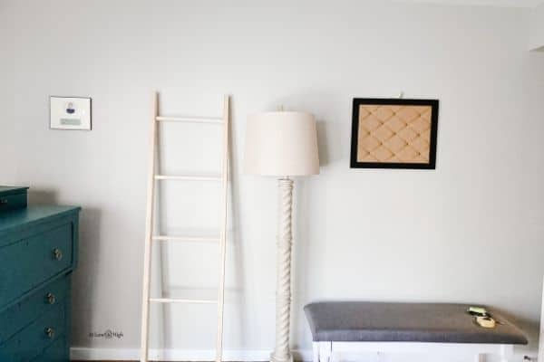 The unfinished blanket ladder leaning on a light gray wall next to a floor lamp.